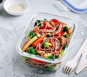 Meal prep containers with broccoli, carrots, rice or soba noodles